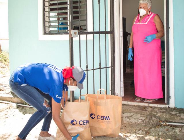 """Con el propósito de contribuir a paliar los efectos del COVID-19, especialmente entre las comunidades más vulnerables, el Consorcio Energético Punta Cana Macao (CEPM) y su subsidiaria la Compañía de Electricidad de Bayahibe (CEB), ambas pertenecientes a la multinacional InterEnergy Group, han iniciado una campaña de donaciones de alimentos de primera necesidad, que se extenderá semanalmente durante el periodo de emergencia, con el objetivo de impactar más de 500 familias de su zona de concesión. Como parte de esta iniciativa, la compañía se ha sumado a la campaña #YoMeQuedoEnCasa de la Fundación Doughty y Jochy Fersobe, a través de la cual se repartirán semanalmente, durante el periodo de emergencia, bonos alimenticios, valorados en RD$1,500 cada uno, a un total de 100 familias procedentes de las comunidades más necesitadas de Bávaro. Adicionalmente, se ha creado un operativo de entregas a través de los voluntarios de CEPM y CEB de paquetes de alimentos básicos, con el propósito de llegar a más de 400 familias de los sectores de Boca de Chavón, Las Lagunas de Nisibón, Altos de Friusa, Matamosquito, Villa Playwood y Villa Europa III, entre otras, que en muchos casos no tienen acceso en estos momentos a establecimientos comerciales. De esta forma, podrán tener garantizados productos básicos de alimentación y evitar que tengan que salir de sus hogares. Gracias a la labor de los voluntarios de la empresa, se están tomando todas las medidas de seguridad para garantizar la salud de los colaboradores y familias beneficiadas, entregando, además, equipos de seguridad, compuestos por mascarillas, guantes y desinfectantes. Esta campaña forma parte de las medidas que ha puesto en marcha esta compañía bajo el programa """"Tu Hogar Seguro"""", para apoyar a las comunidades más vulnerables a los efectos de esta crisis sanitaria, a través de iniciativas como la  donación de energía, el refuerzo de las medidas de seguridad para prevenir contagios y orientación sobre ahorro energético, par"""